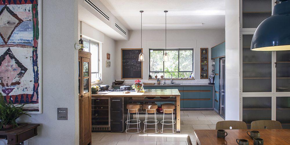 8מבט מפינת האוכל אל כיוון המטבח - אי עבודה וישיבה - תעשייתי - חם - משלב פח מושחר עץ מבוקע מדפי רשת  ונירוס